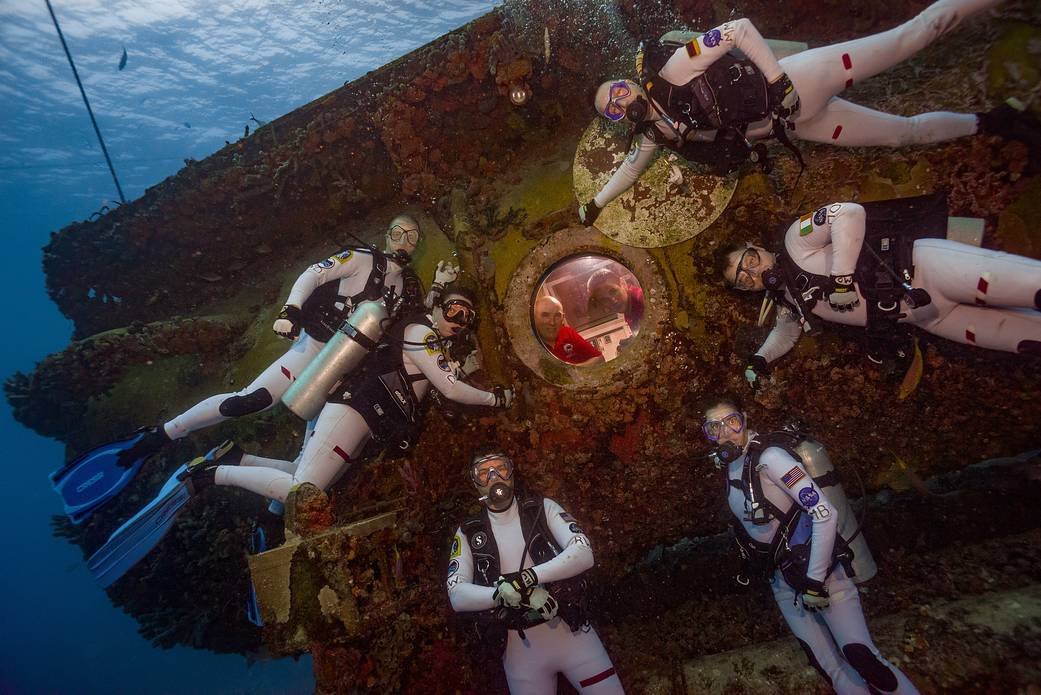 Aquanauts in dive suits pose for photo outside undersea habitat