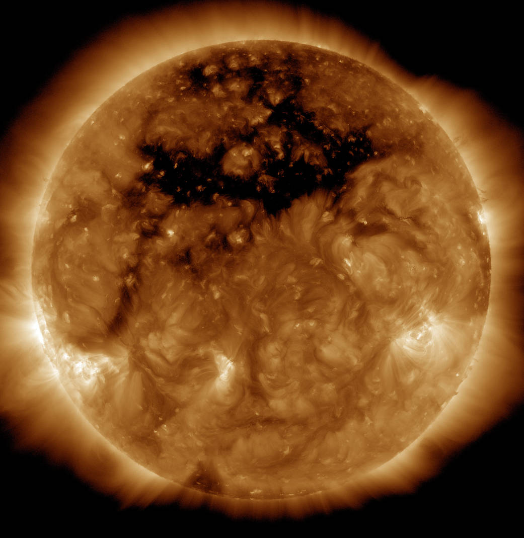 The dark area across the top of the sun is a coronal hole