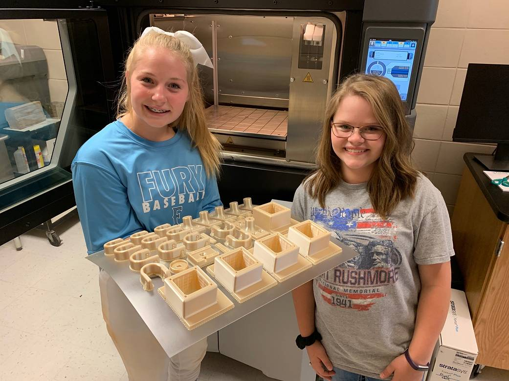 Dade County, Georgia, Middle School HUNCH students KK Castleberry, left, and Meleah Smith show 3D-printed items.