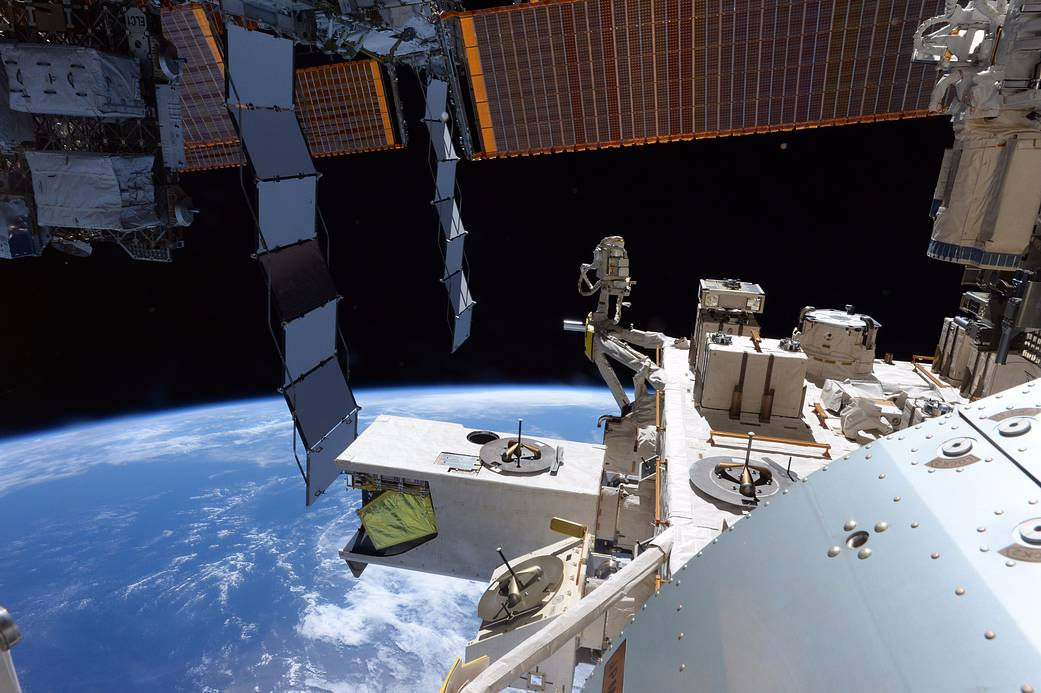 View of Earth from space station with solar arrays and station modules visible