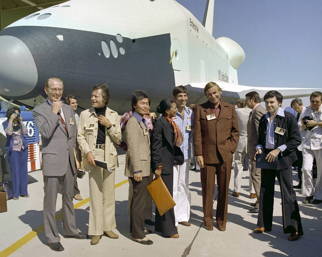 In this image, the then Dryden Flight Research Center (now Armstrong) hosted the Star Trek crew in 1976 for the rollout of Space Shuttle Enterprise posing with the  cast is then NASA Administrator James Fletcher and show creator, Gene Roddenberry.