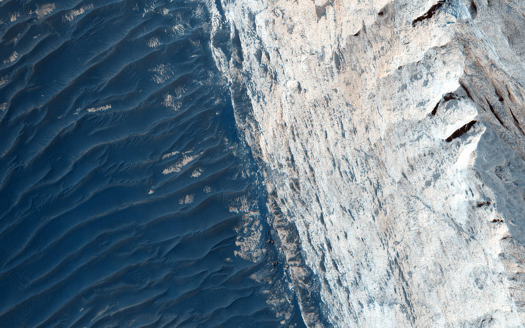 Sedimentary layers on Mars surface in blue tones on left half of image and white on right