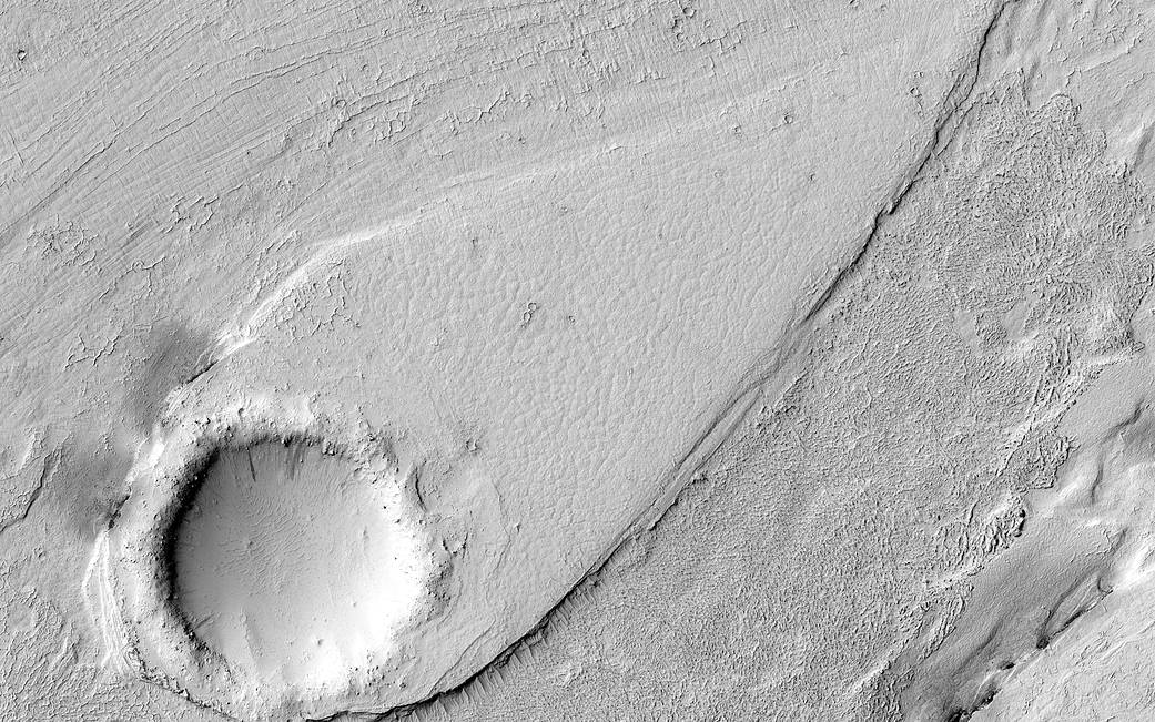 Gray circular form at lower left with channel of dune on Mars surface