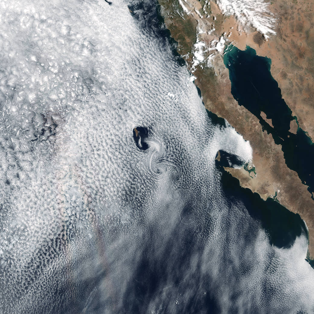 Satellite image of cloud swirls over islands