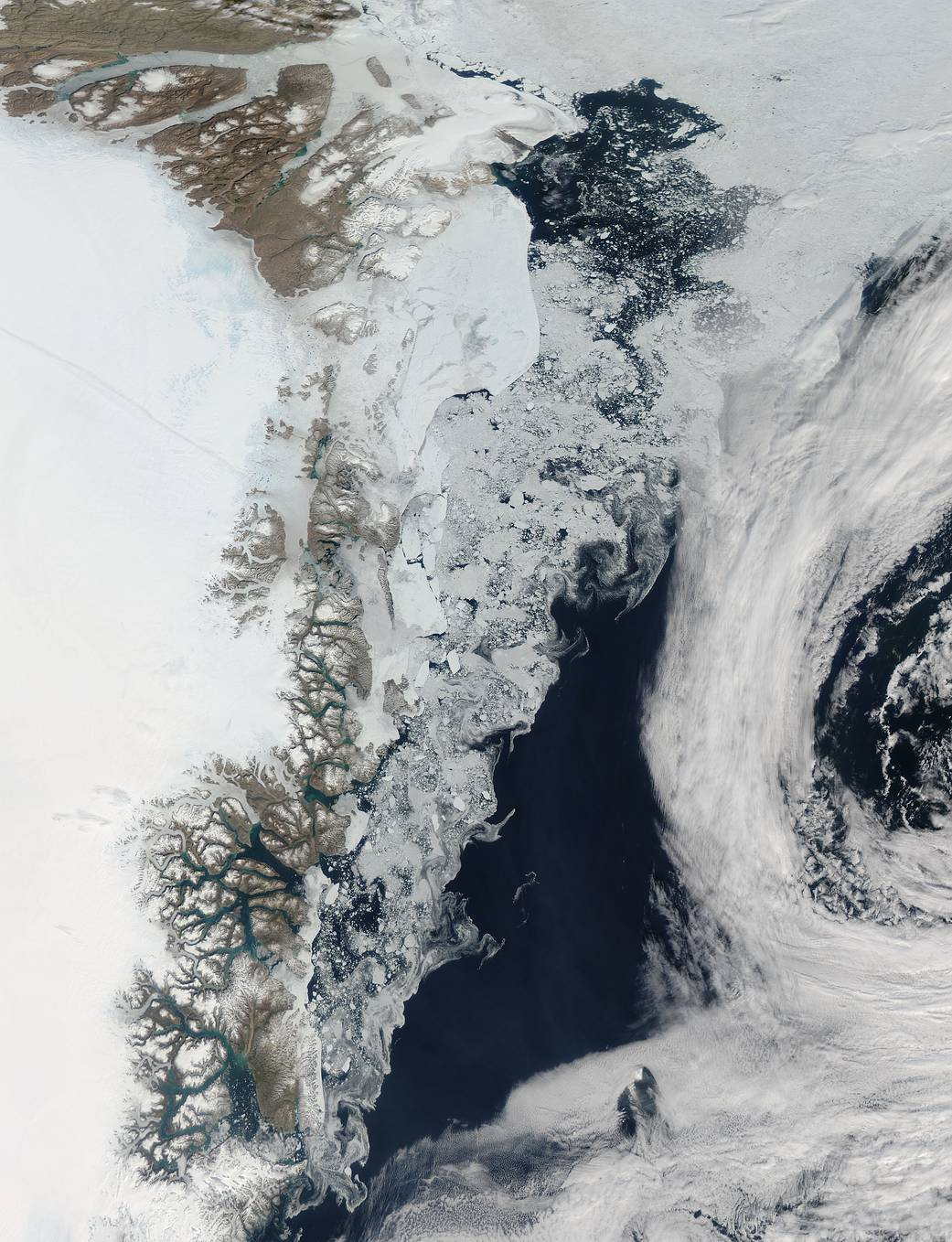 Swirls of sea ice along the coast and dark blue waters of the Arctic
