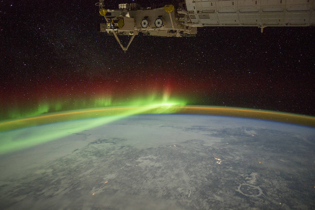 Aurora in brilliant green photographed from orbit with Earth below and crater visible on landscape