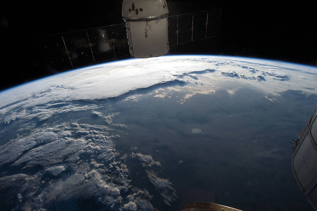 Sunrise over Earth with canyon and clouds below and docked spacecraft at top of frame