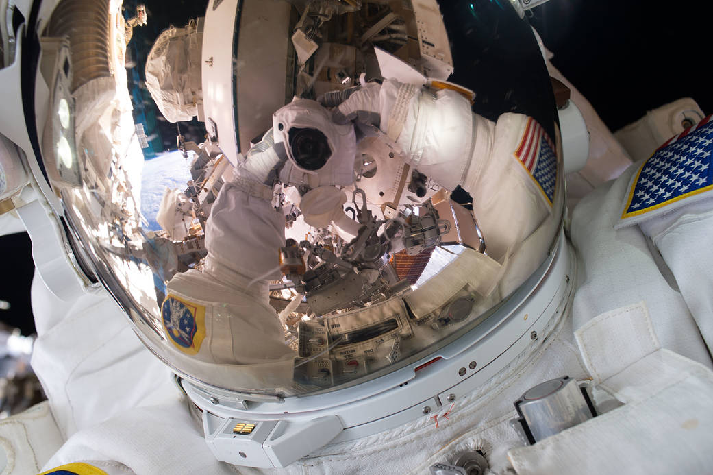 Astronaut photograph reflected in space helmet visor during spacewalk