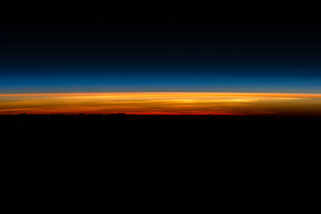 Beginning of sunrise over dark horizon
