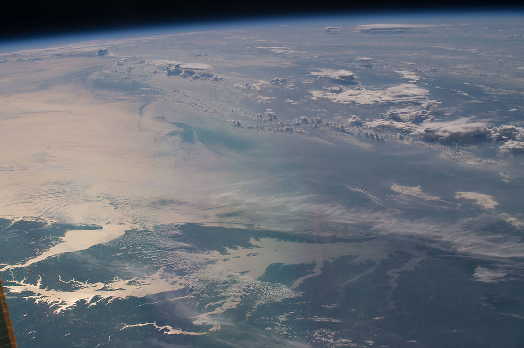 Sunglint over waters of the Chesapeake Bay with clouds overhead, photographed from orbit