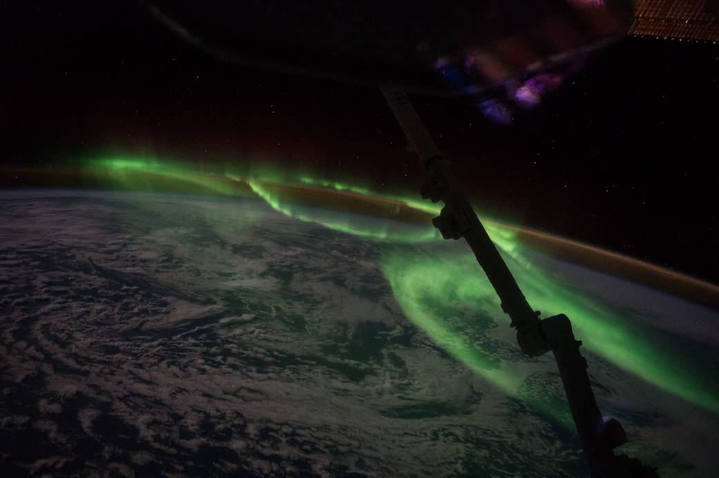 Looping green aurora over Earth with clouds and sea visible below