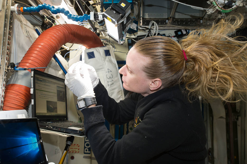 NASA astronaut Kate Rubins looking at DNA sample inside space station laboratory