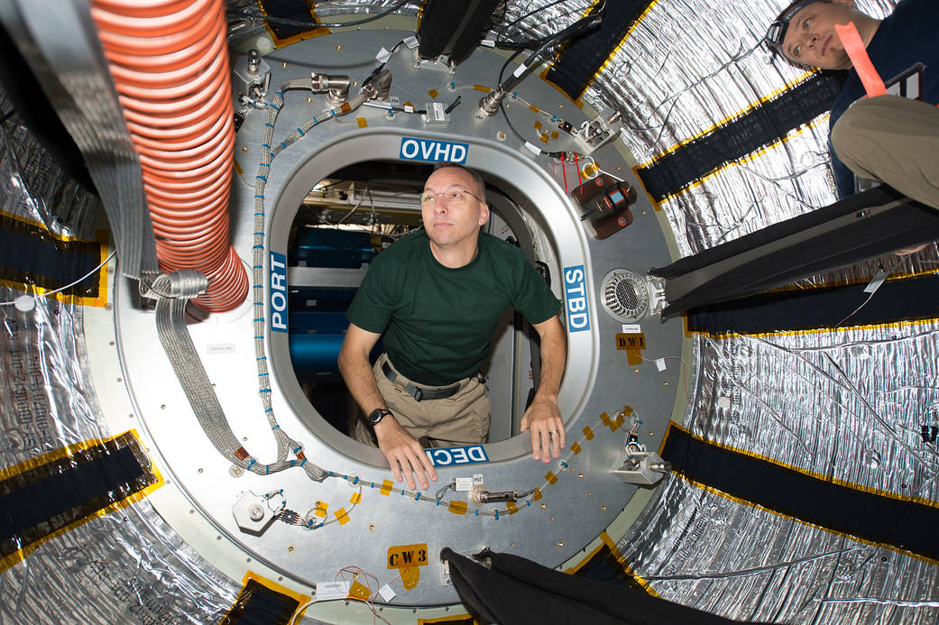 Astronaut floats through hatch of module inside space station