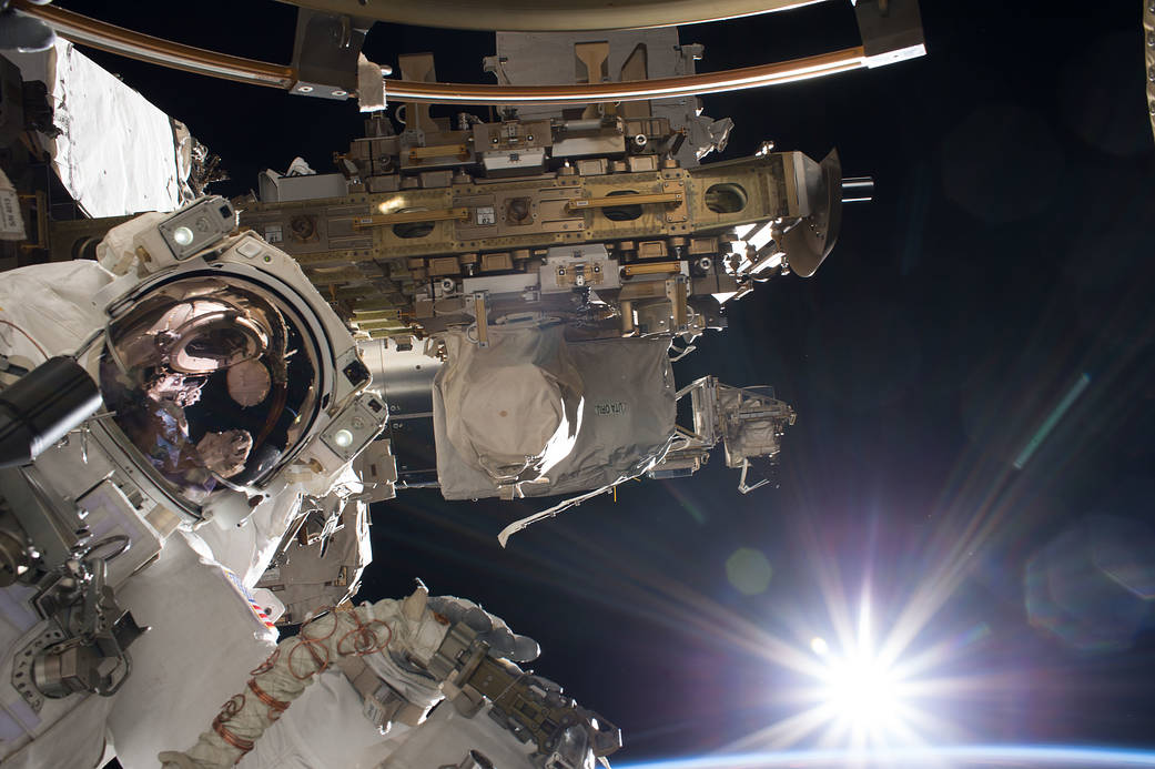 Astronaut in spacesuit at work outside space station module with rising sun in background