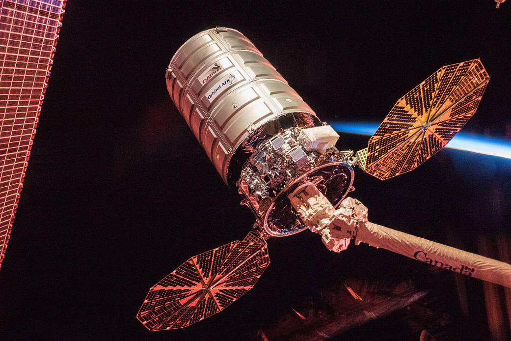 Undocked Cygnus spacecraft at end of robotic arm with solar arrays deployed