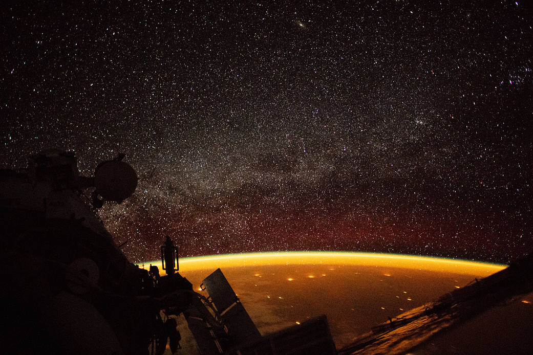 orange hue enveloping Earth is known as airglow—diffuse bands of light that stretch 50 to 400 miles into our atmosphere