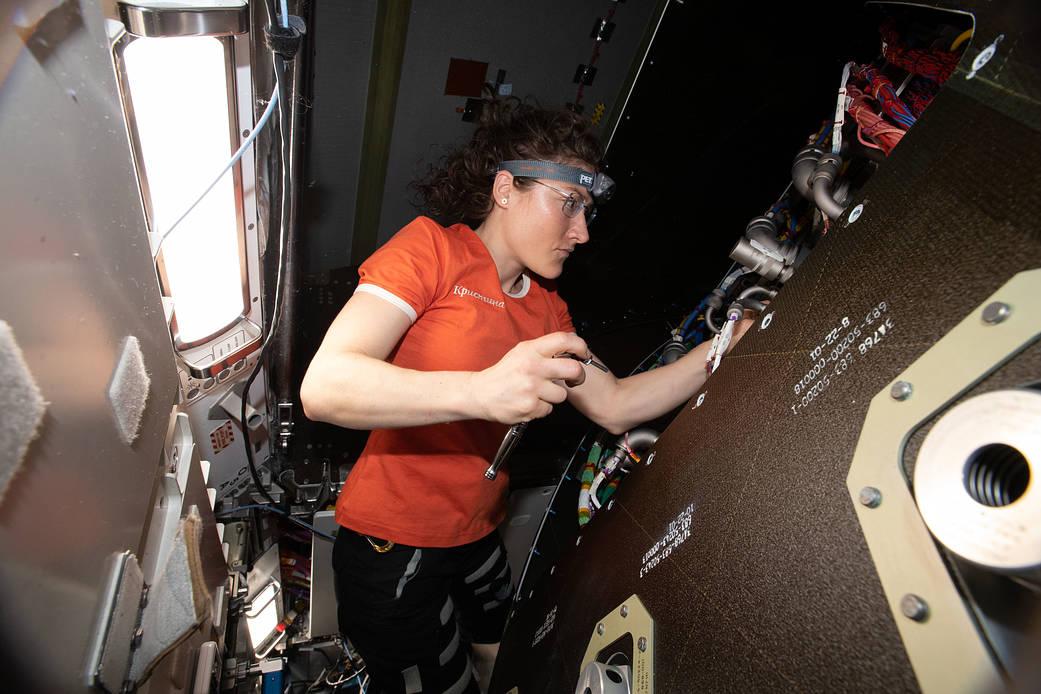 Flight Engineer Christina Koch removes audio hardware