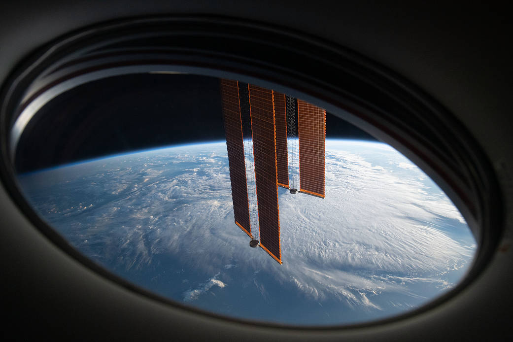 The station's solar arrays drape across the Earth's horizon