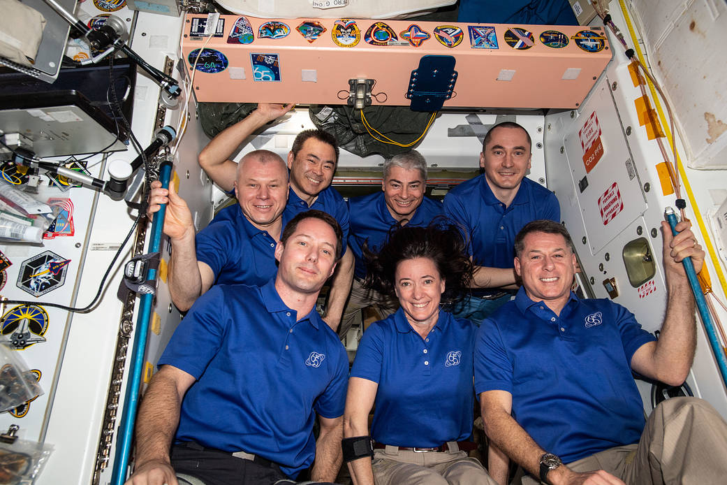 The seven-member Expedition 65 crew gathers for a portrait