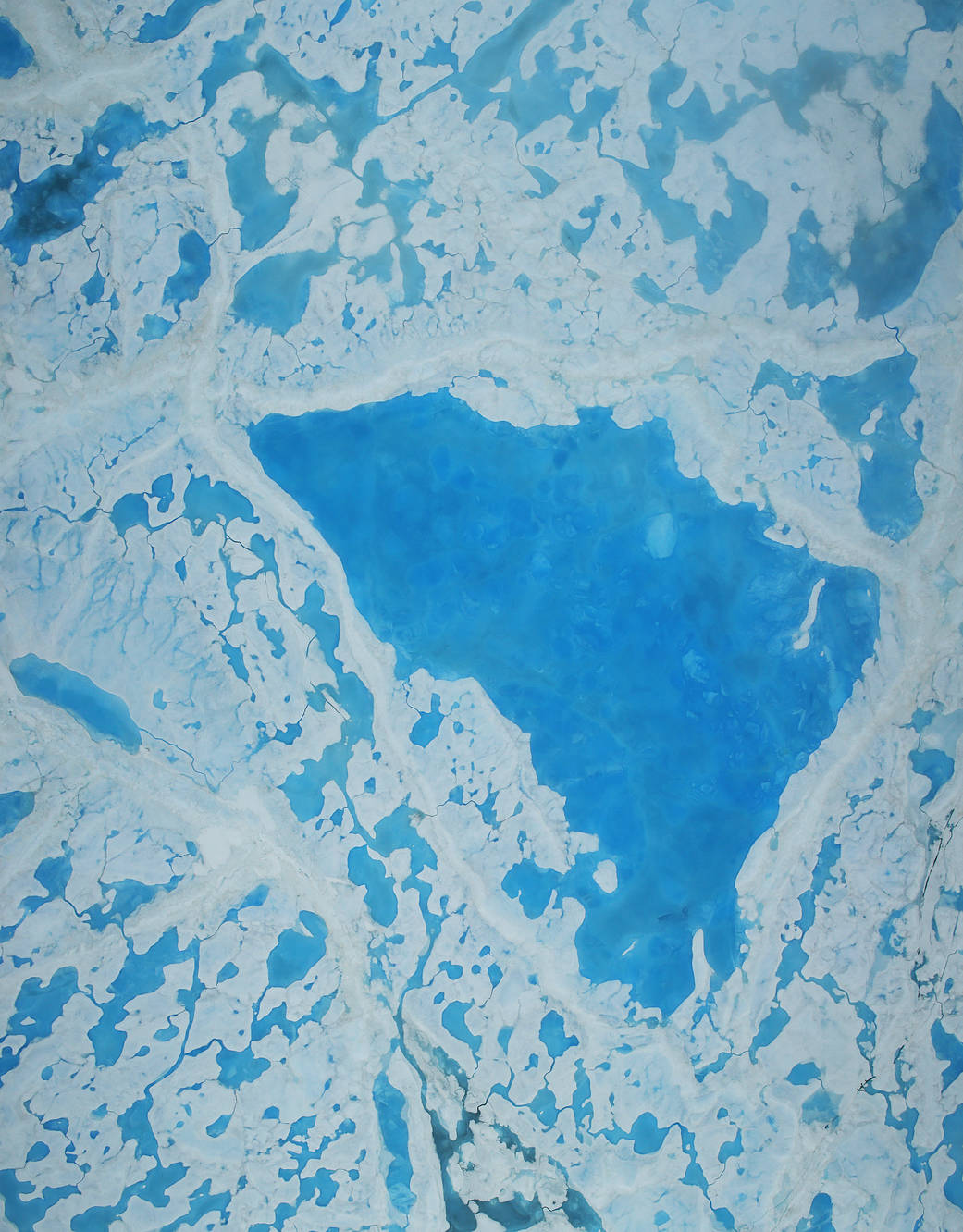 overhead view of sea ice with a large melt pond