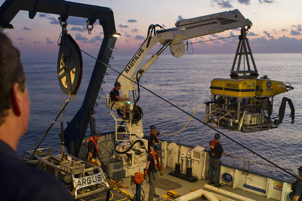 Photo of two remotely operated vehicles for deep sea exploration, seen aboard a ship, one being lifted by a crane into the water