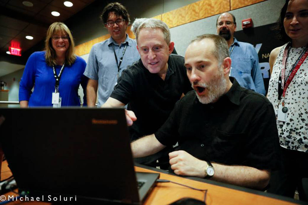 Science team members react to the latest image of Pluto at the Johns Hopkins University Applied Physics Lab on July 10, 2015.