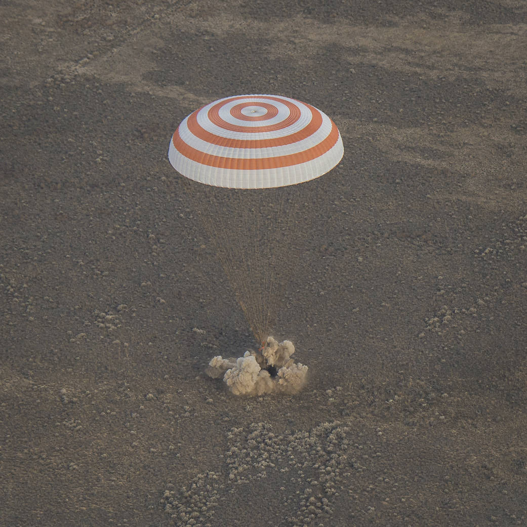 Soyuz touches down with parachute overhead