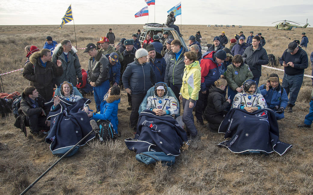 Expedition 49 crew members in chairs outside Soyuz
