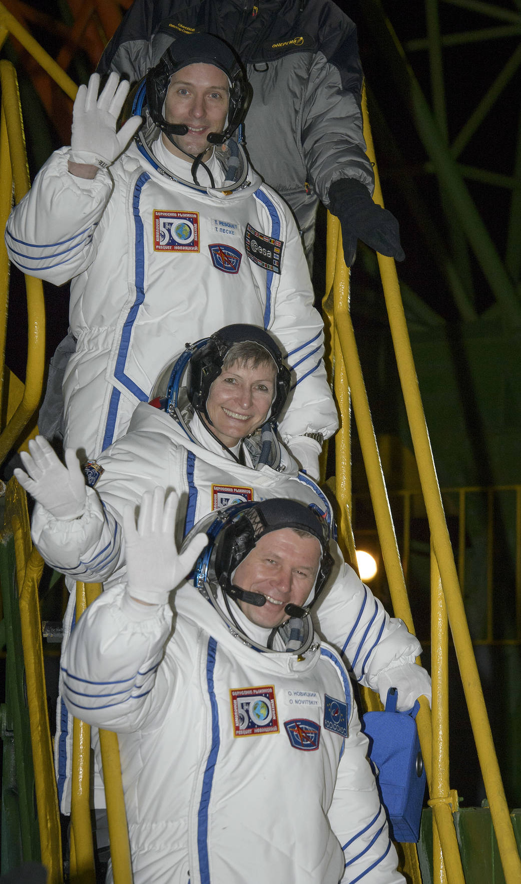 Three crew members in Sokol suits wave from ladder leading to Soyuz capsule