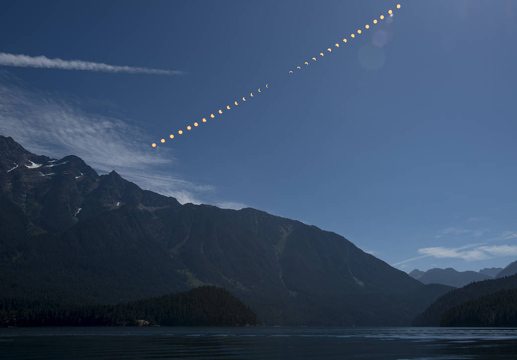 This composite image progression of a partial solar eclipse over Ross Lake, in Northern Cascades National Park, Washin