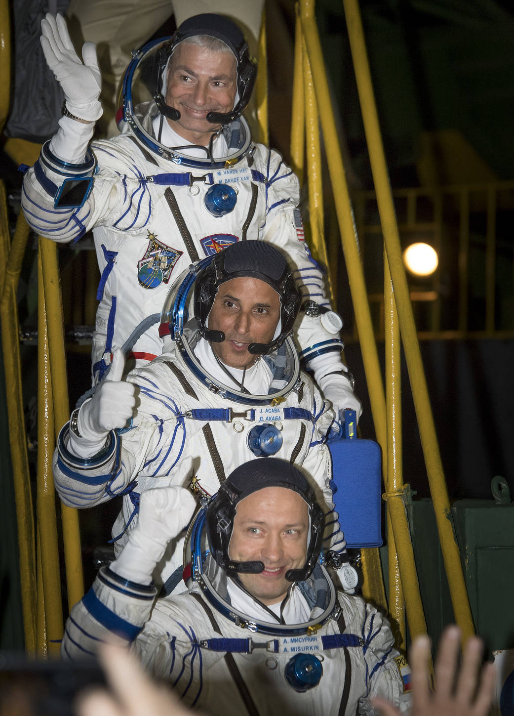 Three astronauts in Sokol suits wave farewell before boarding Soyuz