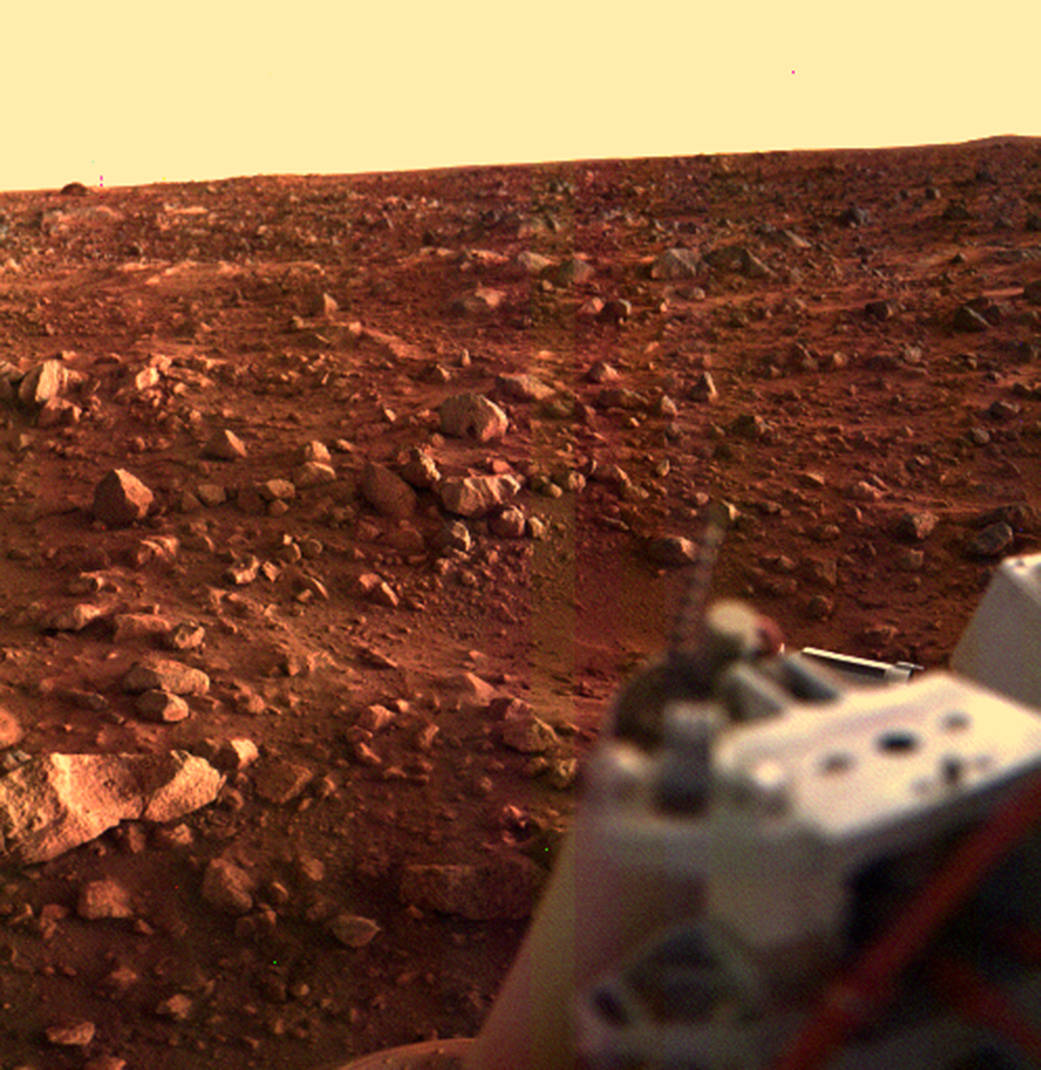 Color image of rocky Martian surface with portion of Viking Lander in lower right corner