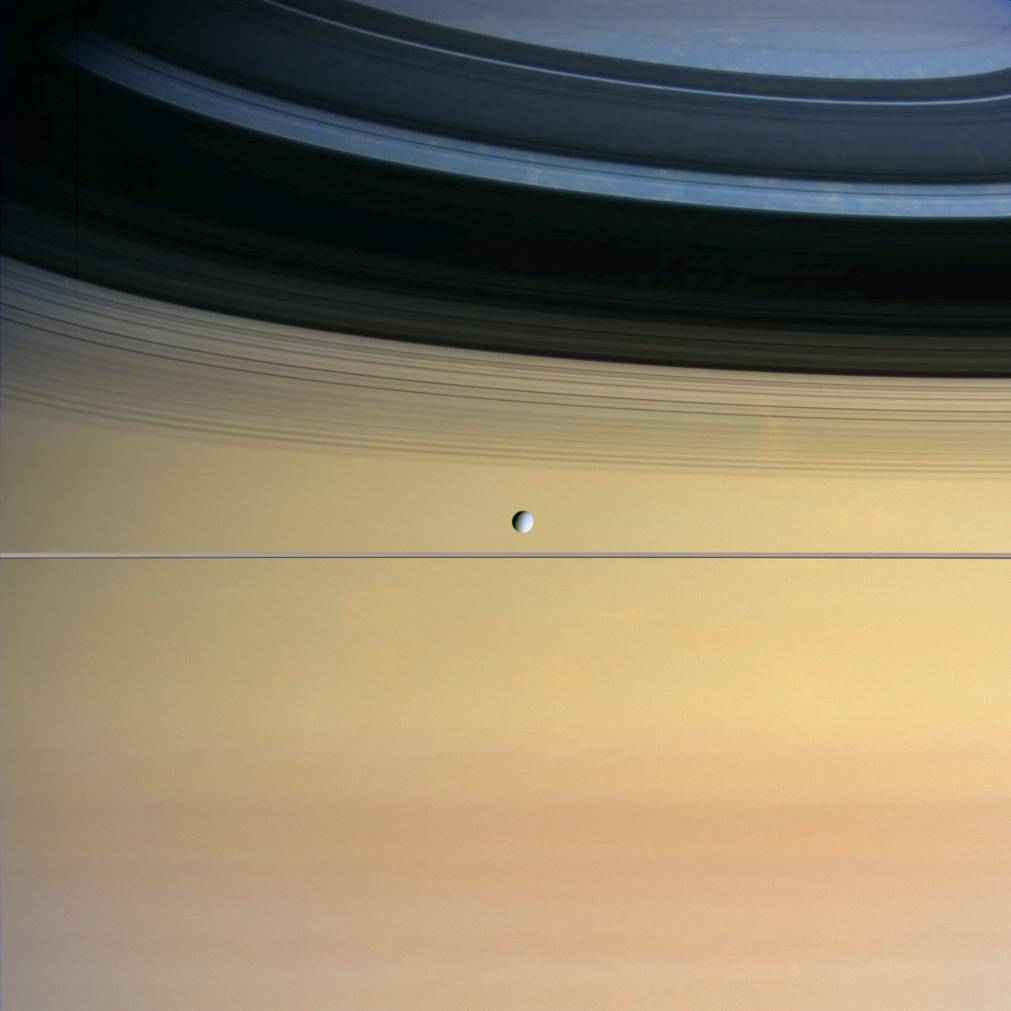 Moon Dione visible in front of large planet Saturn