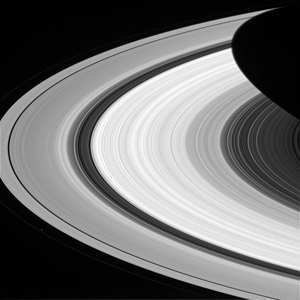 Arc of rings on one side of Saturn in grayscale
