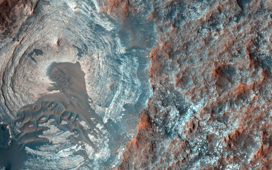 Circular depression in flat Mars surface with smaller crater indentations on right