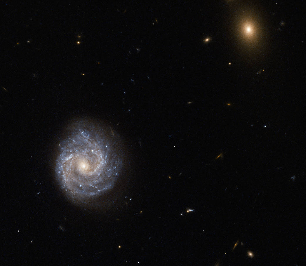 two galaxies, on big and blueish, the other small and gold.