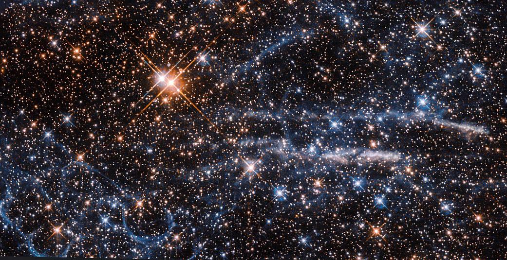 bright stars, wispy blue waves and orange mass