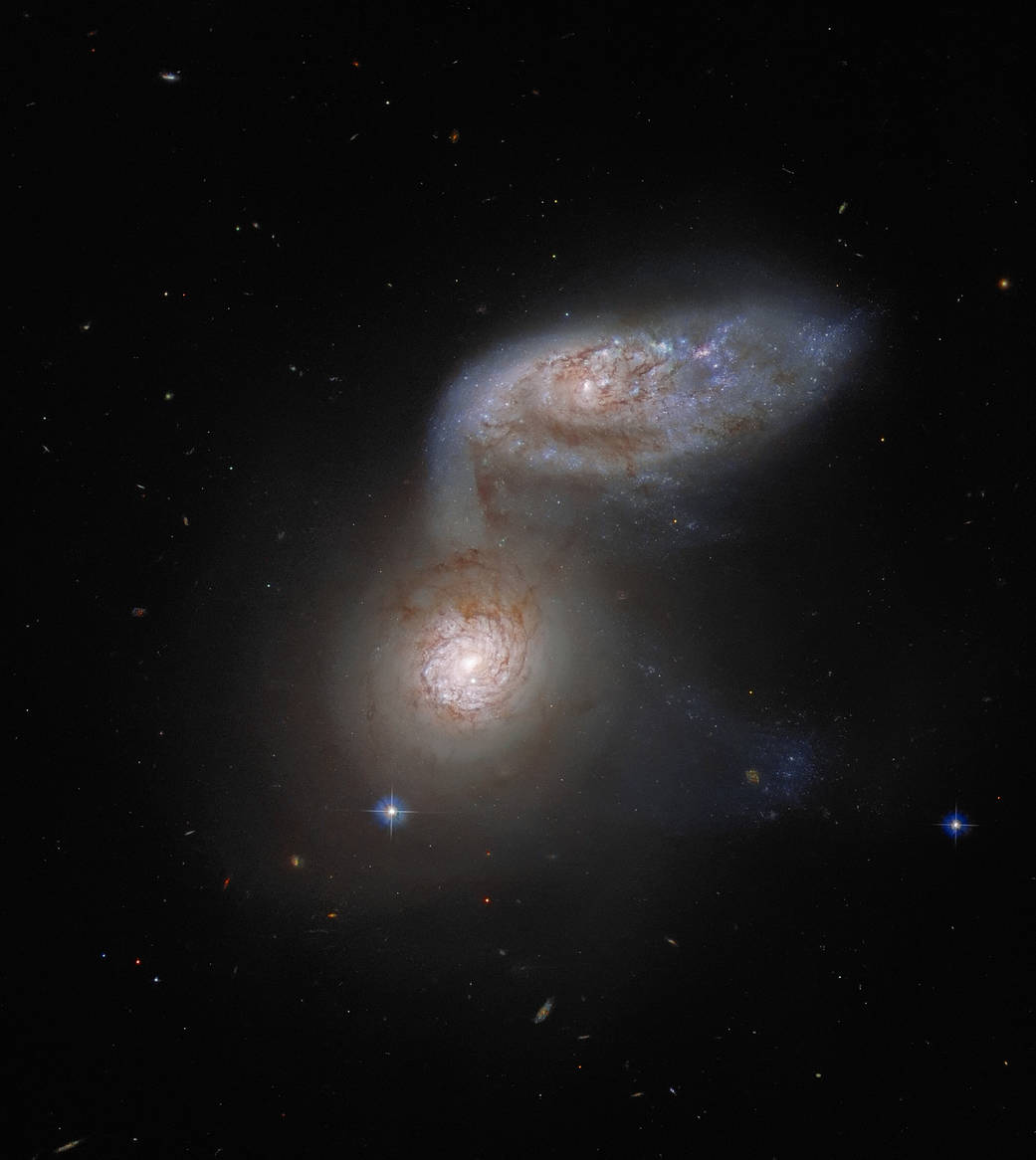 This NASA/ESA Hubble Space Telescope image features two interacting galaxies that are so intertwined, they have a collective name – Arp 91. Their delicate galactic dance takes place more than 100 million light-years from Earth.