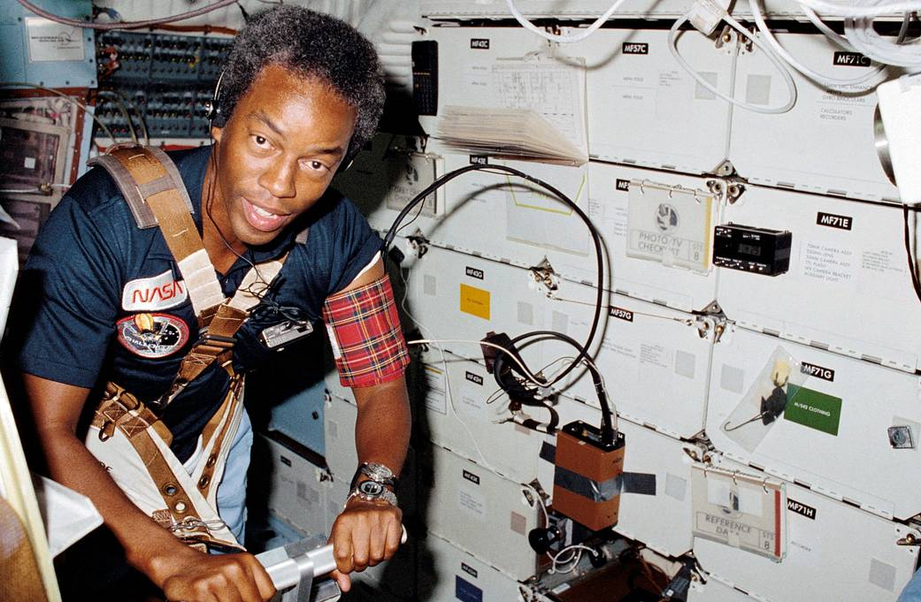 Guion S. Bluford assists with a medical test that required the use of a treadmill exercising device designed by the STS-8 medica
