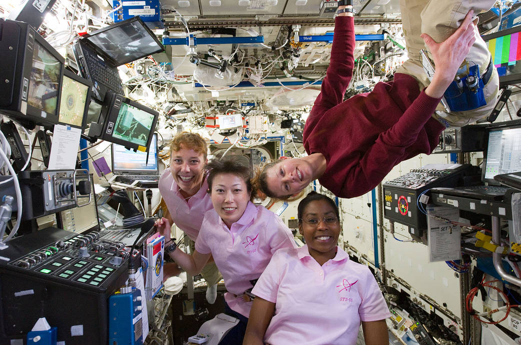 NASA astronauts and JAXA astronaut at work inside International Space Station's Robotics Workstation