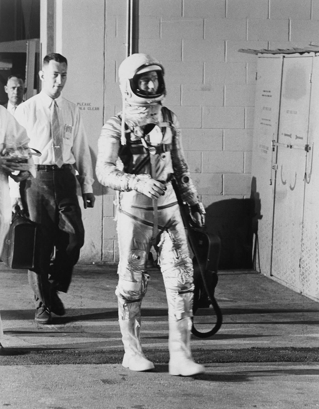 Scott Carpenter in spacesuit walks out of building toward launch site