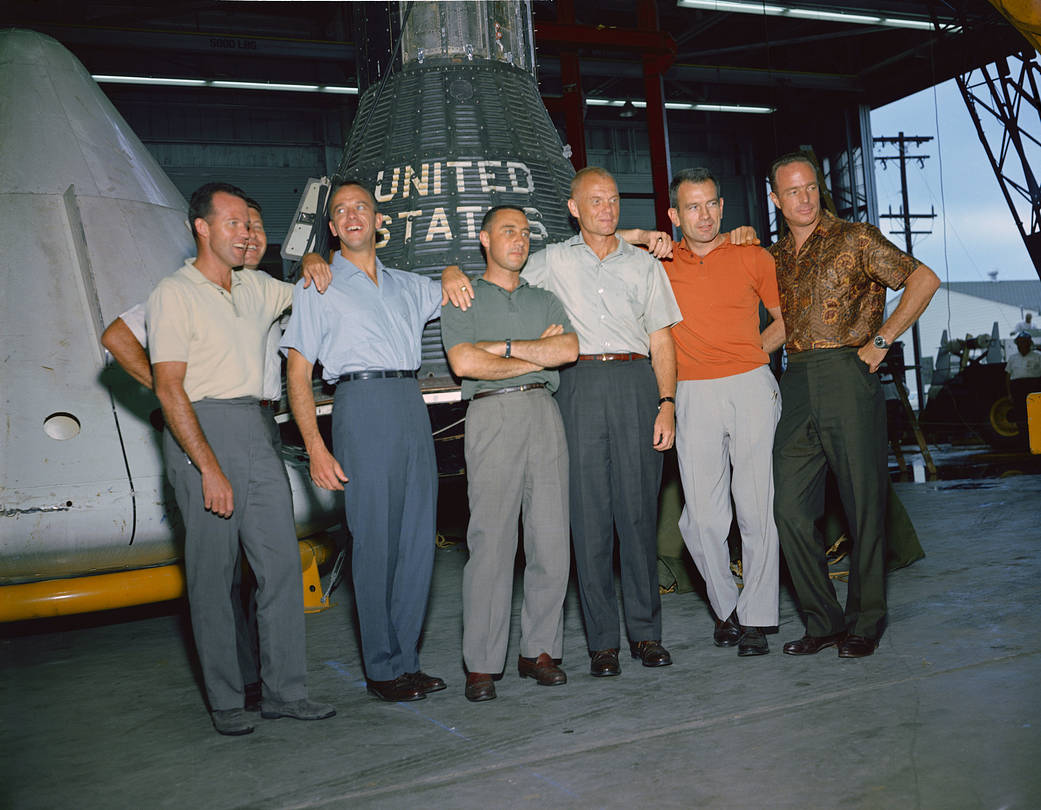 Original Mercury astronauts stand in group for photo in front of spacecraft