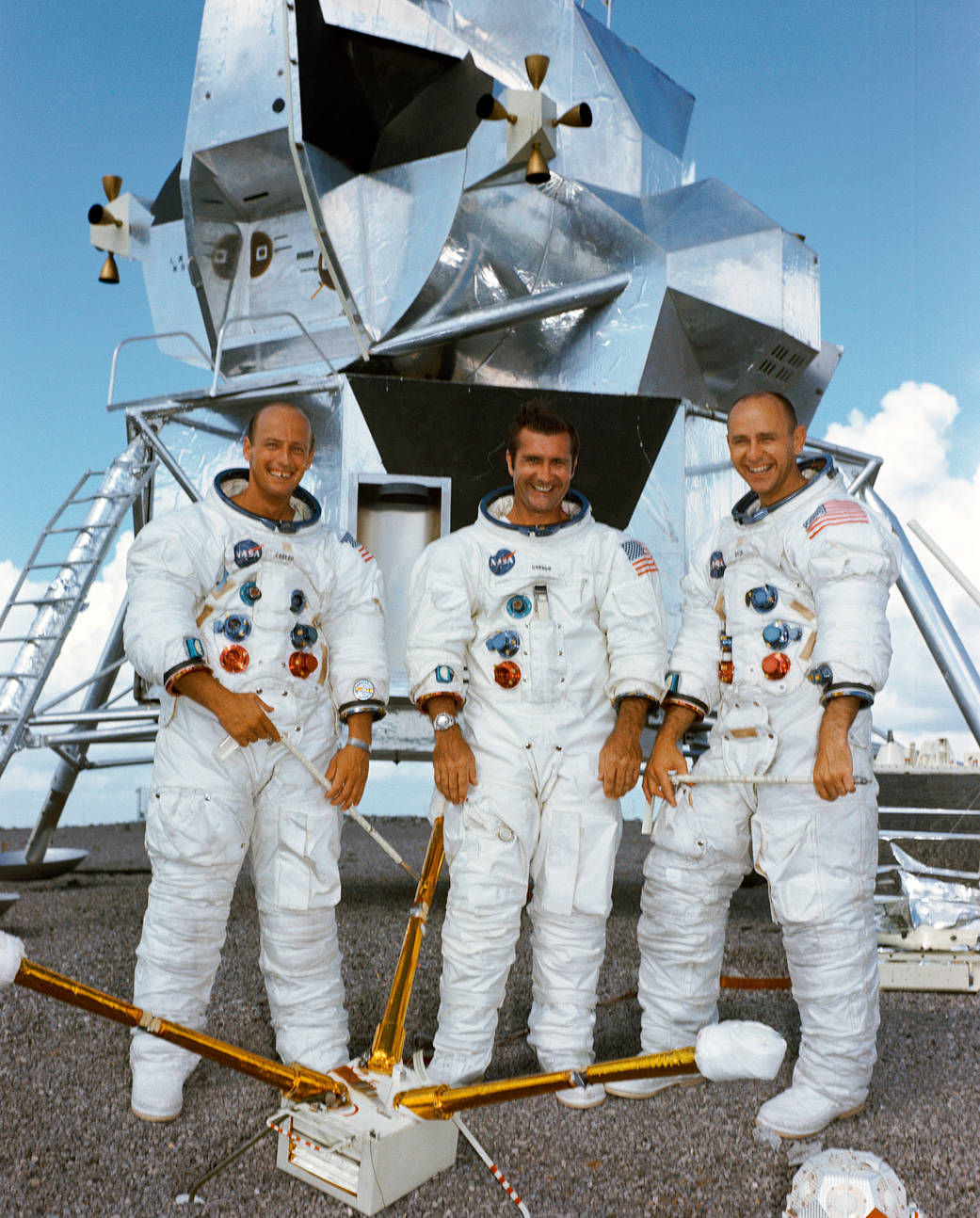 Apollo 12 crew portrait in spacesuits with lunar lander mockup