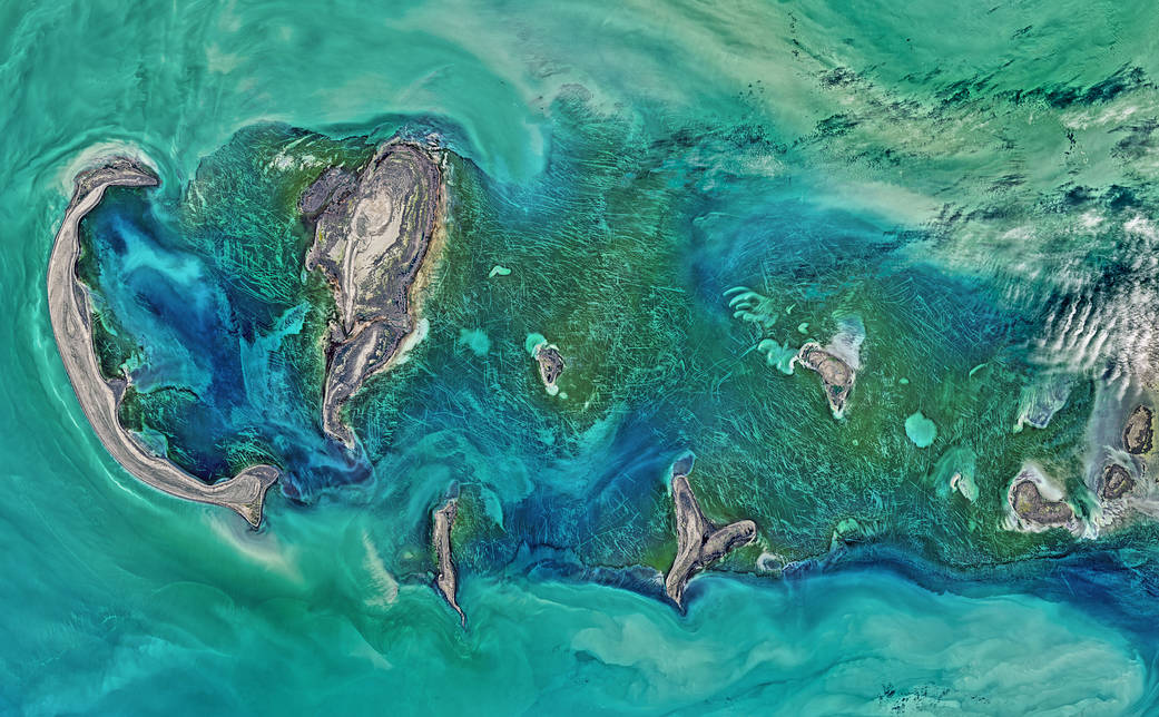 Satellite image of sea with islands and lines scoring along ice