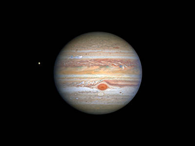 banded Jupiter with Great Red Spot and comparatively tiny moon Europa at left
