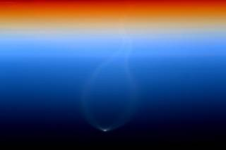 Earth's atmosphere at sunset with bright spot of rocket launch visible below