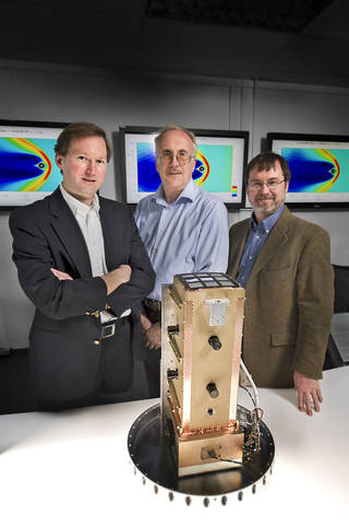 Three people stand behind a piece of space hardware