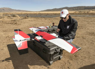 pilot nealing near drone airplane ready for test flight