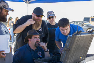Jonathan Adams, from left, John Bodylski, Justin Hall, Caitlin Kennedy and Dave Berger watch a computer screen.