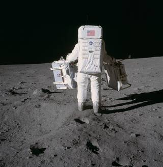 Astronaut Edwin E. Aldrin Jr. moves toward a position to deploy two components of the Early Apollo Scientific Experiments Packag